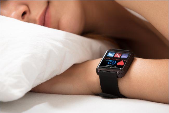 Une femme qui dort pendant qu'une smartwatch montre son rythme cardiaque.