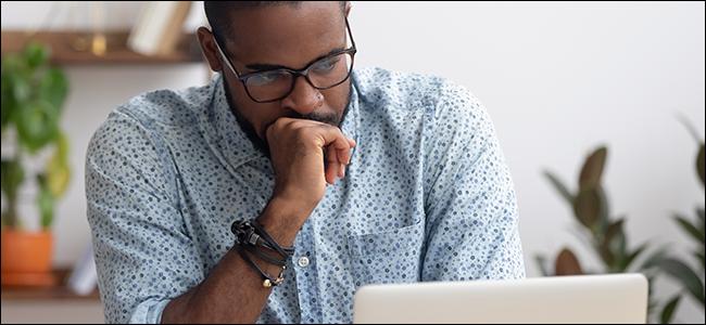 Un homme posant sa main contre sa bouche et regardant un ordinateur portable.