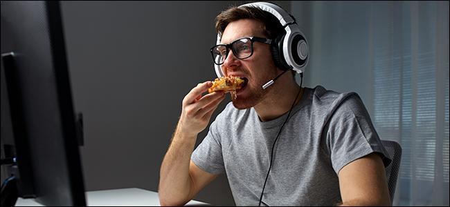 Un homme assis devant un ordinateur, portant un casque et mangeant de la pizza.
