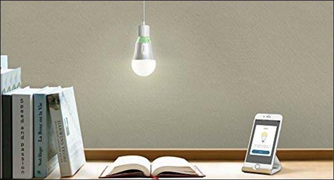 Une ampoule Wi-Fi TP-Link suspendue au-dessus d'un livre ouvert et d'un téléphone portable sur un bureau.