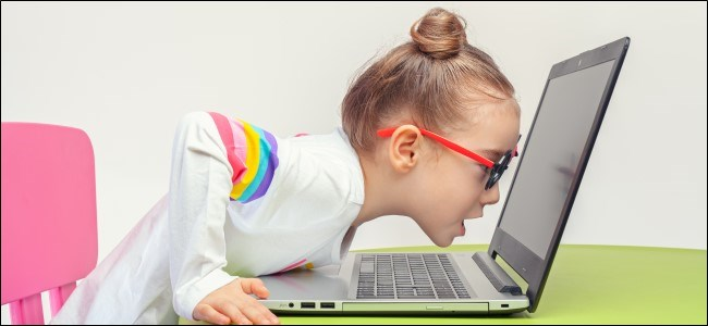 Kid dans des lunettes se penchant sur un ordinateur portable