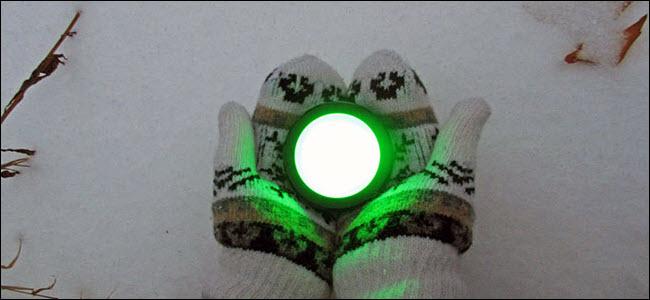 Une paire de mains gantées tenant un bouton Echo vert brillant sur la neige.