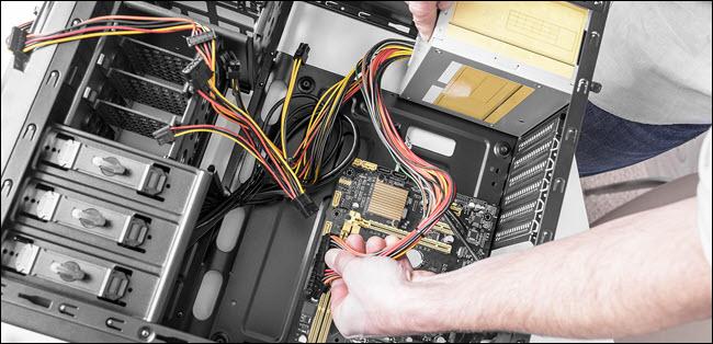 technicien installant une alimentation dans un PC