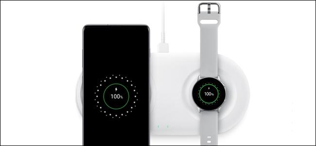 Un téléphone Samsung et une montre sur un chargeur.