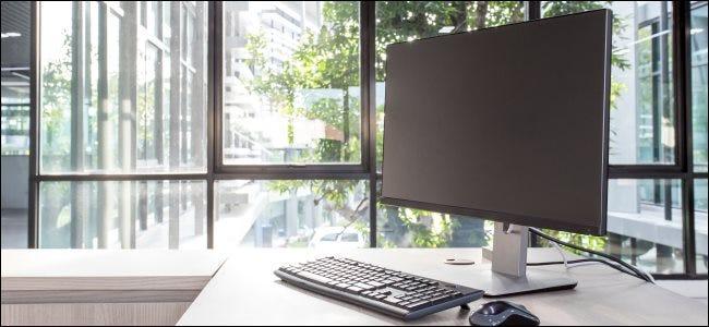 Un écran d'ordinateur, un clavier et une souris sur un bureau.