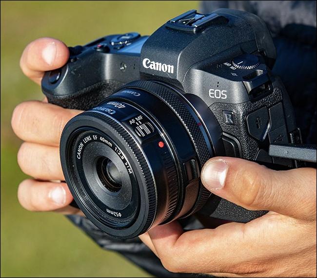 Quelqu'un tenant un appareil photo Canon EOS avec un adaptateur sans miroir monté dessus.