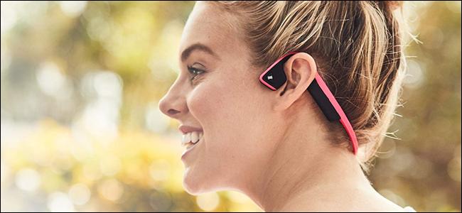 Une femme portant des écouteurs à conduction osseuse AfterShokz.  Elle a l'air de s'amuser, mais elle est peut-être en train de rebuter un passant.