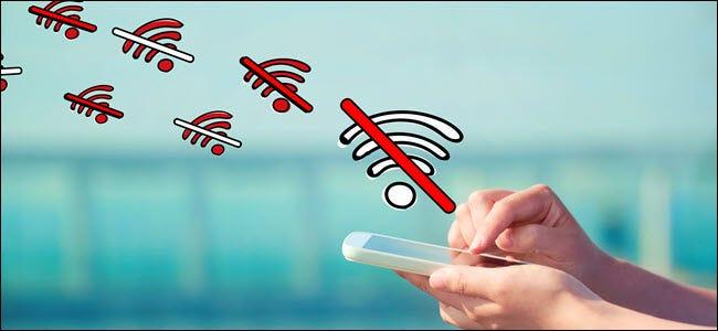 """Mains tenant et appuyant sur un téléphone avec """"Pas de wifi"""" symboles flottant dessus."""