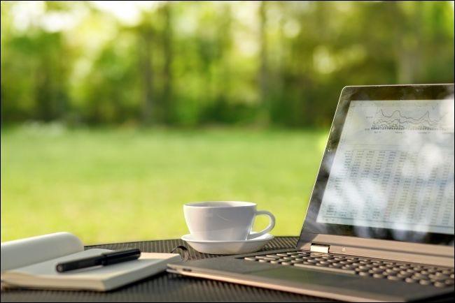 Ordinateur portable et café sur une table à l'extérieur