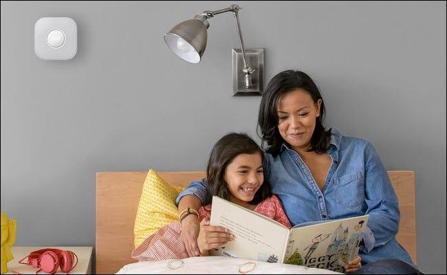 Une mère et son enfant lisant un livre pour enfants au lit, avec un Nest Protect fixé au mur au-dessus de leur tête.