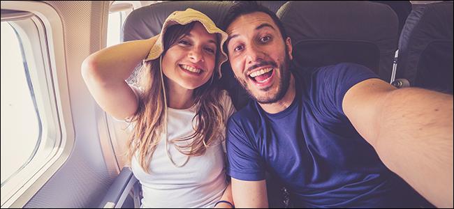 Un jeune couple prenant un selfie dans un avion