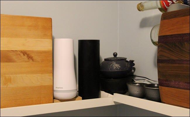 Un Echo à côté d'une théière, d'un SimpliSafe et de deux planches à découper.