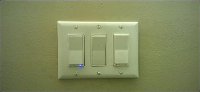 Trois interrupteurs d'éclairage, un avec une lumière bleue révélant qu'il est intelligent.