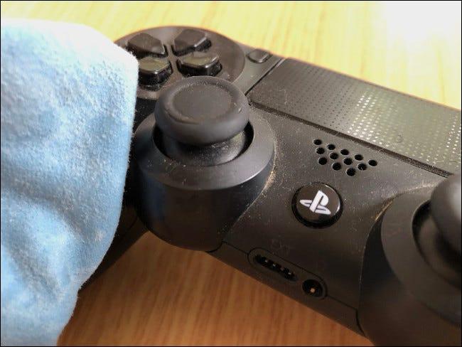 Un chiffon essuyant un contrôleur DualShock 4.
