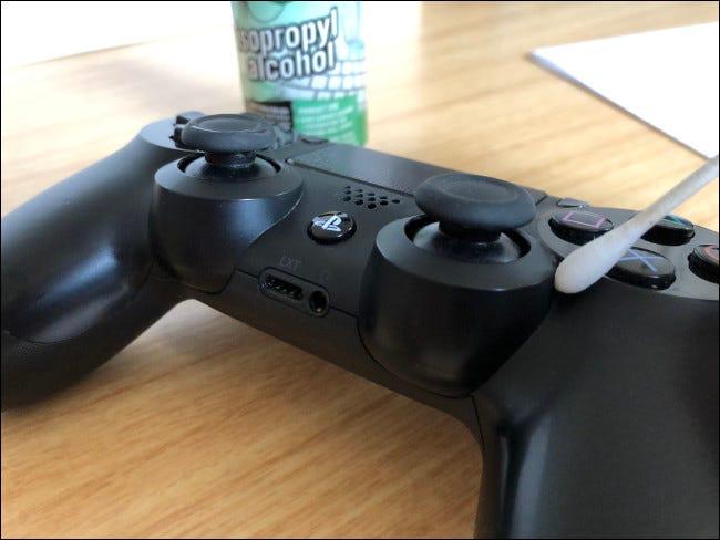 Un contrôleur DualShock 4 avec un Q-tip sur le dessus à côté d'une bouteille d'alcool isopropylique.