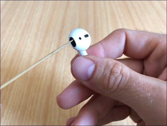 La main d'un homme tenant un AirPod et nettoyant le haut-parleur avec un cure-dent.