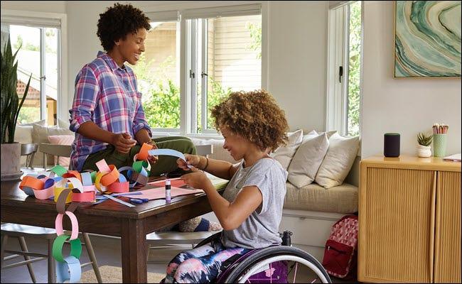 Un jeune enfant dans un fauteuil roulant faisant de l'artisanat avec sa mère à une table avec un Amazon Echo à proximité.
