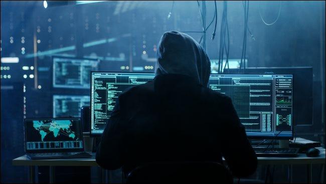 Un hacker ténébreux dans un sweat à capuche assis devant un ordinateur.