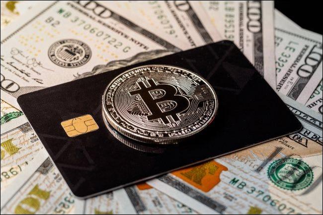 Un jeton Bitcoin physique au-dessus d'une carte de crédit posée sur des billets de 100 $.