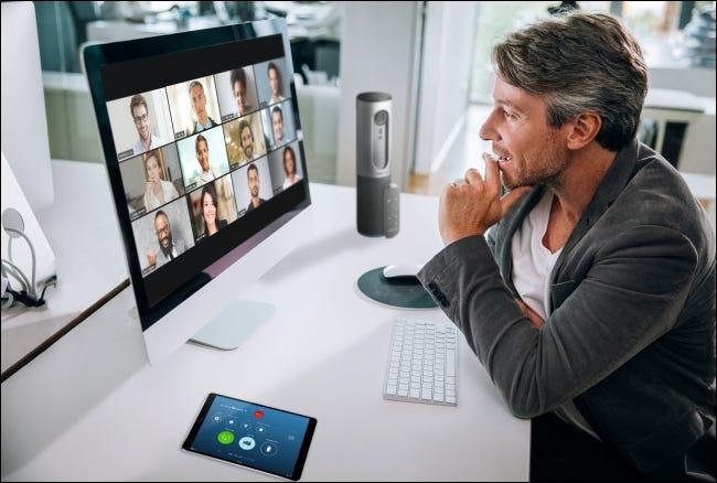 Un homme sur une réunion Zoom sur son Mac avec les participants en vue Galerie sur le moniteur.