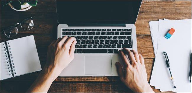 Mains tapant sur un ordinateur portable.