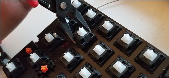 Quelqu'un tirant un mécanisme d'interrupteur à clé d'un clavier avec des pinces.