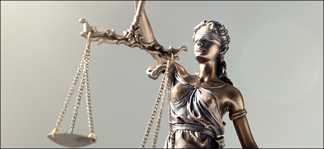 """Une statue de """"Justice,"""" une femme aux yeux bandés tenant les échelles métaphoriques de la loi."""
