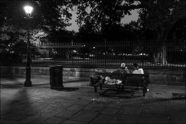 deux hommes assis sur un banc de parc la nuit;  un homme dormant sur un siège derrière eux