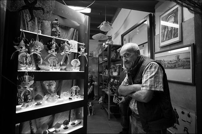 Homme plus âgé aux bras croisés dans la boutique de curiosités