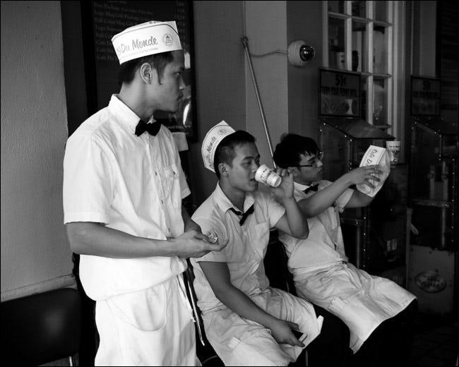 Trois employés de restaurant discutant à l'extérieur pendant une pause