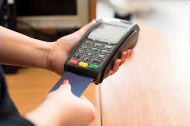 Femme payant par carte de crédit en boutique ** Remarque: Soft Focus à 100%, mieux pour les petites tailles