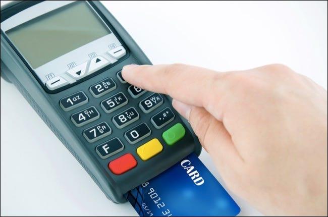 L'homme à l'aide du clavier du terminal de paiement entre le numéro d'identification personnel