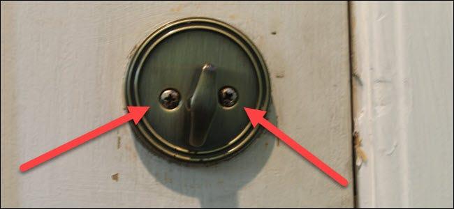 Un pouce standard tourne sur une serrure, avec deux flèches rouges pointant vers deux vis.