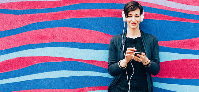 Une femme sourit en écoutant de la musique avec des écouteurs