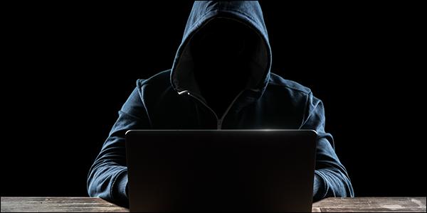 mystérieux homme ringard dans un sweat à capuche piratage dans un ordinateur portable
