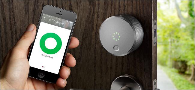 La main d'un homme tenant un iPhone montrant l'application August Smart Lock et ouvrant une porte avec un August Smart Lock dessus.