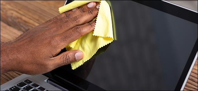 La main d'un homme nettoyant un écran d'ordinateur portable avec un chiffon en microfibre.
