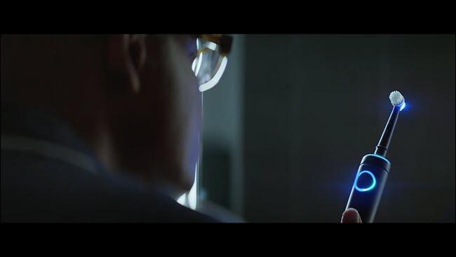 L'homme de la publicité d'Alexa regardant sa brosse à dents Echo illuminée.