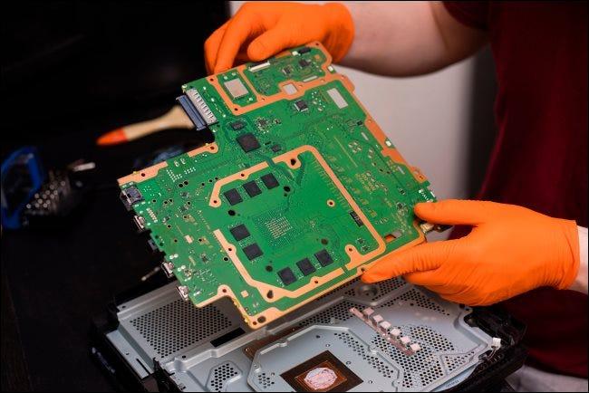 Une personne réparant l'intérieur d'une console PlayStation 4 Pro.