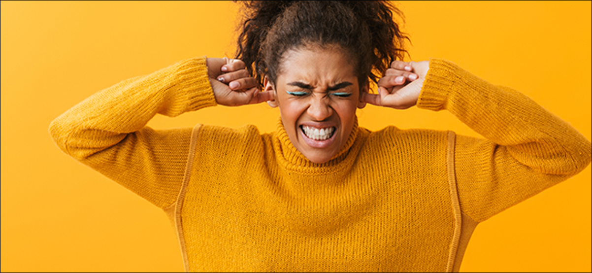 Une femme bouleversée se bouche les oreilles avec ses doigts