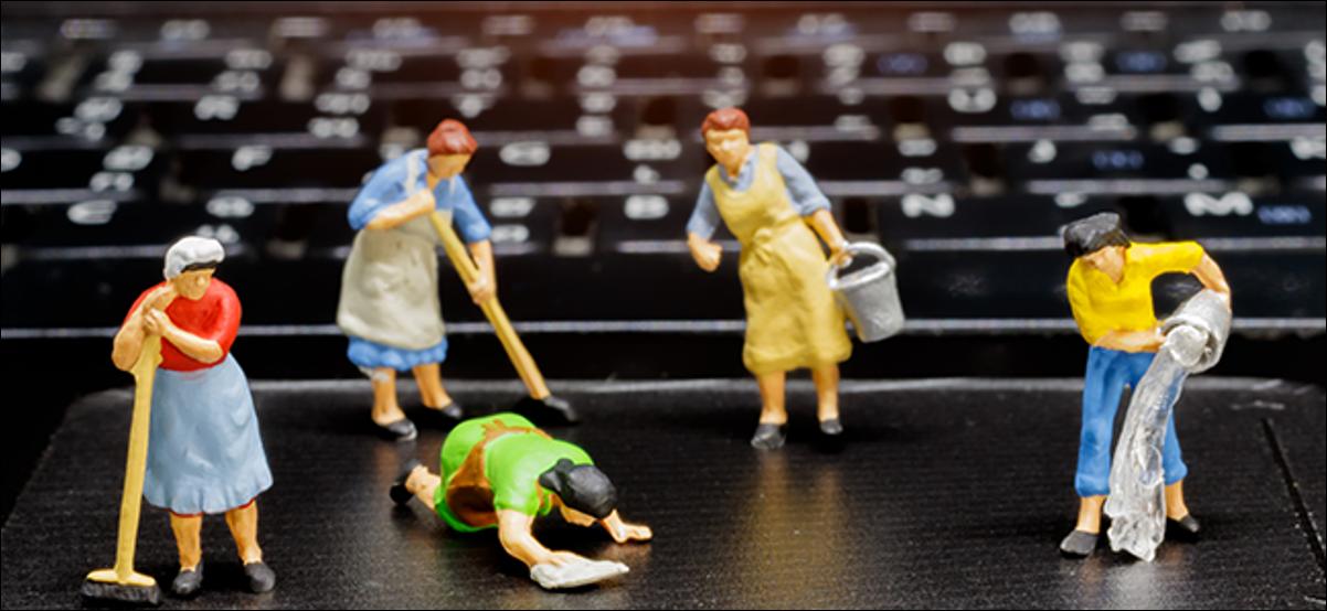 Maids en plastique miniatures nettoyant un ordinateur portable