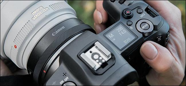 Quelqu'un tenant un appareil photo Canon avec un adaptateur sans miroir.