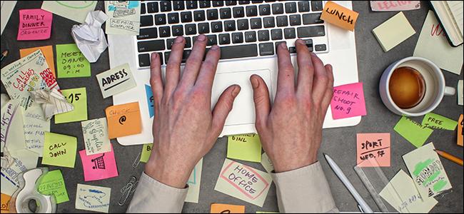 Une paire de mains travaillant sur un bureau extrêmement en désordre.