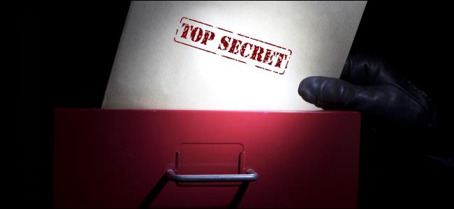 """Une main tirant un document marqué """"Top secret"""" dans un classeur."""