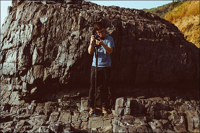Appareil photo de réglage de l'homme sur monopode en face de la falaise
